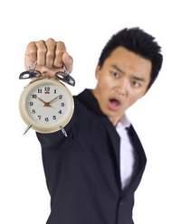 shocked businessman with alarm clock